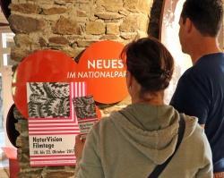 Im Hans-Eisenmann-Haus informieren sich bereits die ersten Besucher über die NaturVision Filmtage Bayerischer Wald 2017. (Foto: Gregor Wolf/Nationalpark Bayerischer Wald)