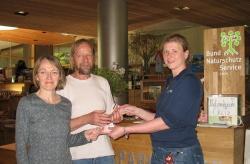 Alexandra Schrötter (rechts) vom Nationalparkladen überreicht Horst Rösing und Rosemarie Wagenstaller vom Bund Naturschutz einen Scheck.