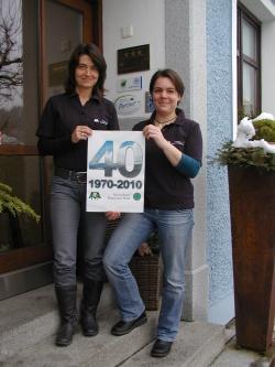 Sandra de Graaf (links) und Britta Baums zeigen mit einem Plakat, dass der 40. Geburtstag des Nationalparks Bayerischer Wald heuer im Mittelpunkt der Nationalpark-Partner-Initiativen stehen wird.