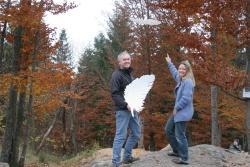 Glaskünstler Ronald Fischer präsentiert seine Schöpfung - eine der 10 Glasfedern, während die Leiterin des Haus zur Wildnis Bärbel Sagmeister zeigt, wo sie in den Baumkronen zu suchen sind.