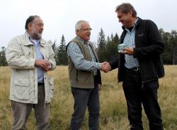 """Klaus Büchler (l.) und Georg Pletl (Mitte) bedanken sich mit einem gläsernen Pflasterstein bei """"Schachten-Hausherr"""" Leibl für die gute Zusammenarbeit"""