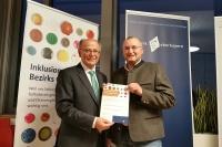 Christian Grassl (r.), Koordinator für Barrierefreiheit im Nationalpark Berchtesgaden, nimmt die Urkunde von Bezirkstagspräsident Josef Mederer (l.) entgegen.